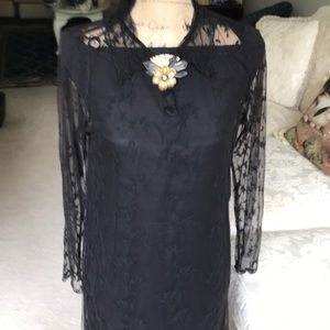 Black lace over black strapless sheath dress.